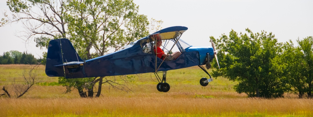 Takeoff of blue ultralight airplane from Belite.