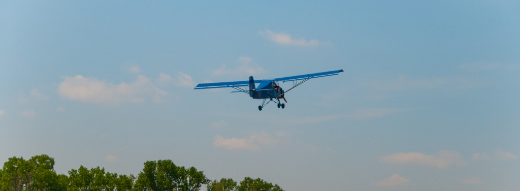 Climbout of blue ultralight airplane from Belite.